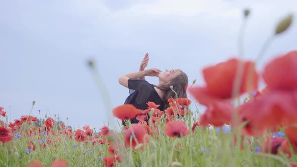 Thumbnail for Pretty Girl Dancing in a Poppy Field Smiling Happily. Connection with Nature. Leisure in Nature