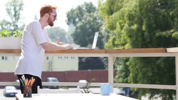 Thumbnail for Young Man Video Conference on Laptop, Chat, Standing in Balcony Outdoor