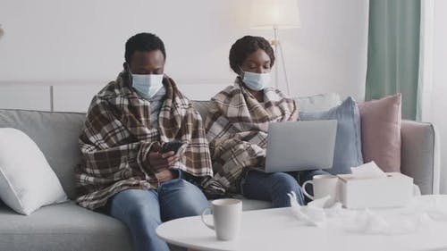 Sick African American Couple Wearing Protective Face Masks Sitting Selfisolated at Home and Working
