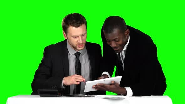 Cover Image for Two Successful Businessman Sit Down at the Negotiating Table in the Office and Working at His Laptop