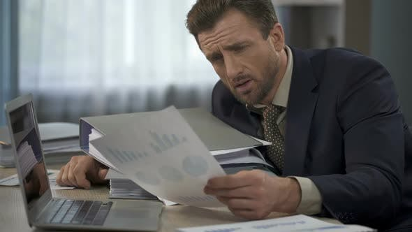Thumbnail for Man Surrounded by Paperwork at Office Looking at Graphs, Head Falling on Folders