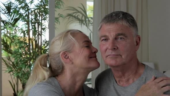 Thumbnail for Woman kissing husband on cheek