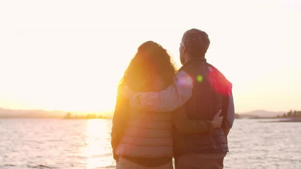 Cover Image for Loving Couple Embracing and Discussing Beautiful Sunset over Lake