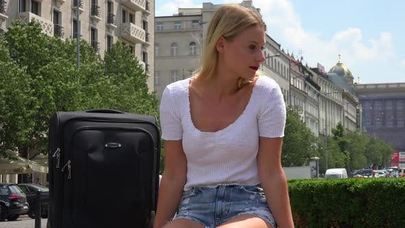 Thumbnail for A Young Beautiful Woman with a Suitcase Looks Around an Urban Area with a Smile