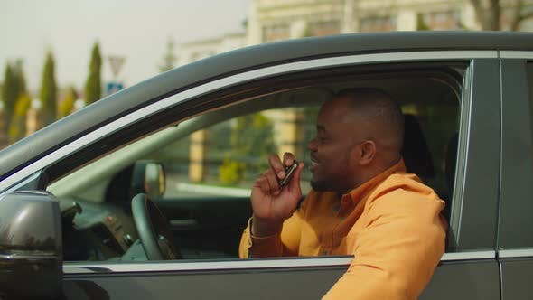 Proud African Male Driver Showing Keys of New Car