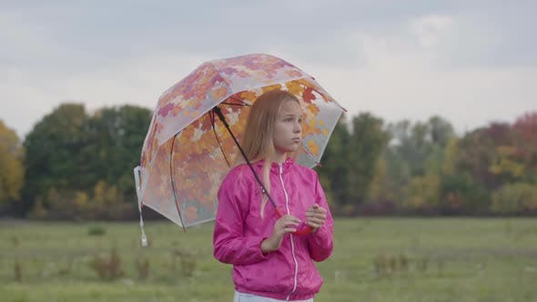 Thumbnail for Sad Caucasian Blonde Girl Dressed in Pink Jacket Holding Collorful Umbrella with Painted Yellow