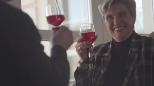 Back of Man with Glass of Red Wine and Portrait of Happy Smiley Senior Woman with Grey Short Hair