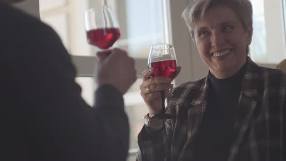 Thumbnail for Back of Man with Glass of Red Wine and Portrait of Happy Smiley Senior Woman with Grey Short Hair