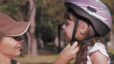 A Woman Puts on a Helmet To a Child.