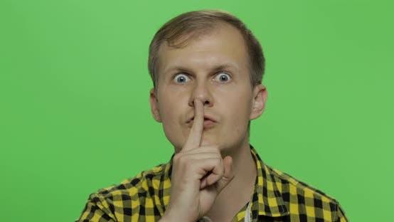 Thumbnail for Man hält ein Geheimnis oder fragt nach Stille, ernstes Gesicht, Gehorsam-Konzept