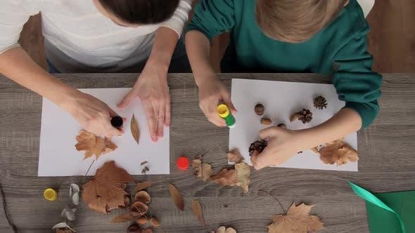 Mutter und Sohn machen Bilder von Herbstlaub