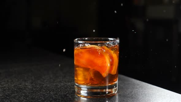 Thumbnail for Falling Ice Cubes Into Glass with Spirit Beverage with Splashes Shot on Black Background. Slow