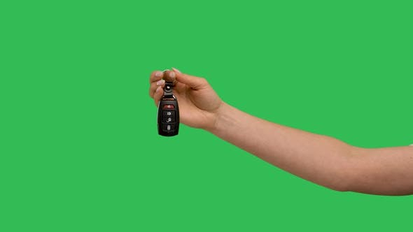Female Hand Holding Car Remote Control Points His Finger at It and Makes Thumb Up Recommendation