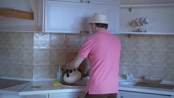 Man in a Hat is Dancing in the Kitchen Pouring Water Into a Kettle Good Mood
