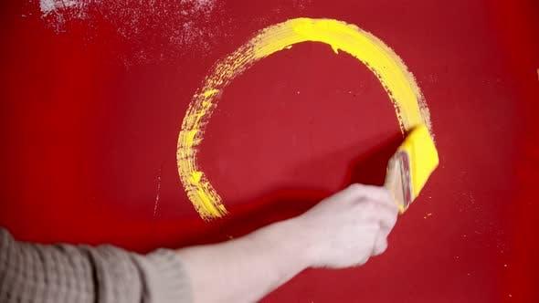 Thumbnail for Eine Person Malerei ein Smiley Gesicht mit einer gelben Farbe auf der roten Wand