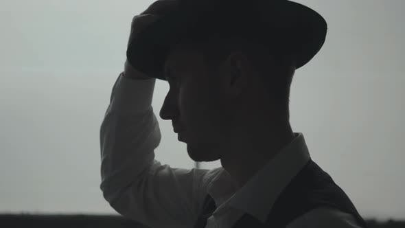 Thumbnail for Side View of Handsome Confident Man Putting a Hat on the Head in Front of Big Window