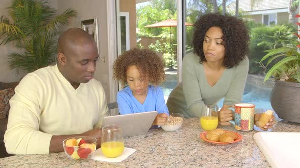 Thumbnail for African American family  eating breakfast and using laptop
