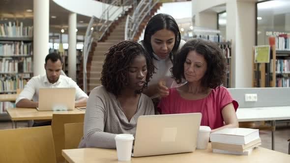 Thumbnail for Vorderansicht von ernsthaften Frauen, die in der Bibliothek arbeiten
