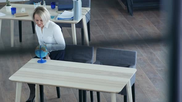 Thumbnail for Blond Businesswoman Looking at Globe in Office