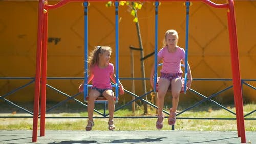 Two girls ride a swing in the Park on a Playground on a summer day