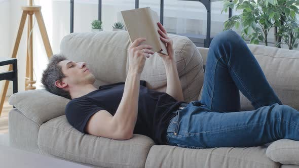 Caucasian Young Adult Smart Man Millennial Guy Male Lies on Soft Comfortable Sofa at Home Living