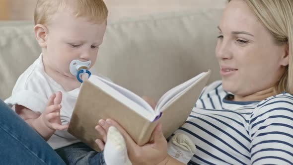 Young Mother Reading Story to Baby
