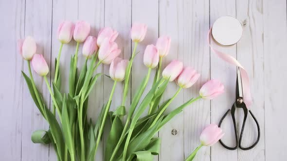 Thumbnail for Step by step. Florist wrapping pink tulips in bouquet