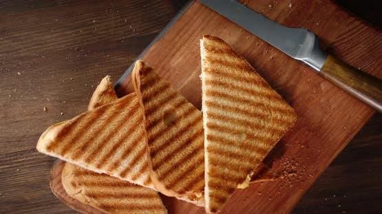 Stücke von gebratenem Brot drehen sich langsam auf den Tisch. Auf einem hölzernen Hintergrund