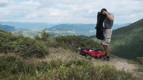 Male Tourist Changes Clothes While Standing on a Mountain Hill with a Backpack