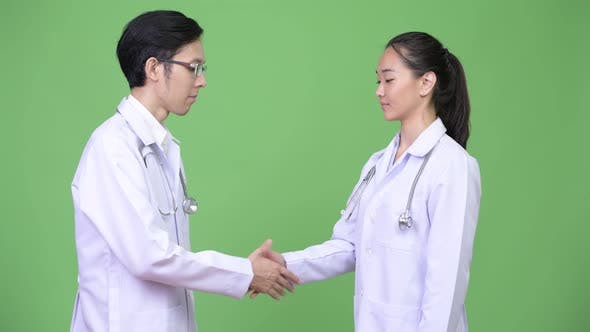 Young Asian Couple Doctors Shaking Hands Together