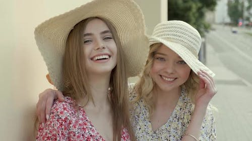 Two young beautiful smiling hipster girls in trendy summer sundress