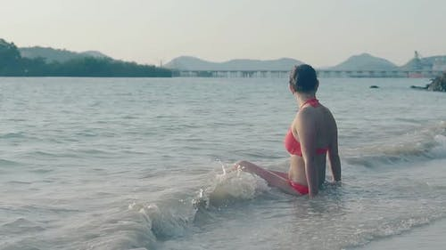 Girl with Perfect Body Rests in Waves in Evening Slow Motion