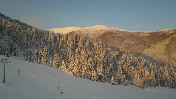 Thumbnail for Flight Over Cable Chair Lift and Pines in Mountain Ski Resort in Winter. Mountains with Pine Trees