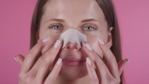 Woman Wearing Nose Patch Looking at Camera