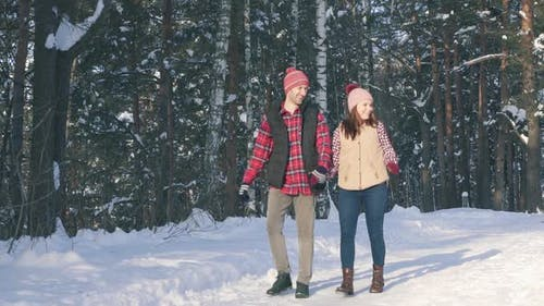 a Couple of Smiling Young People in Winter Clothes in a Snowy Forest on a Sunny Day Strolling