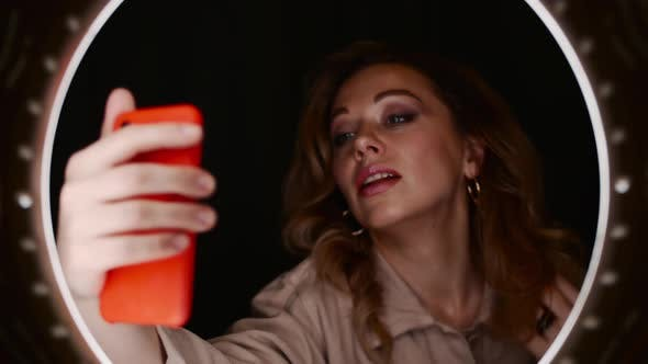 Beauty Blogger Female Holds Smartphone in Front of Ring Light and Takes Selfie