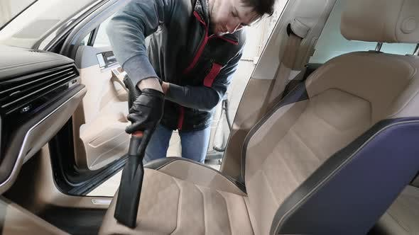 Man Cleaning the Front Seat of a Car Using Vacuum Cleaner