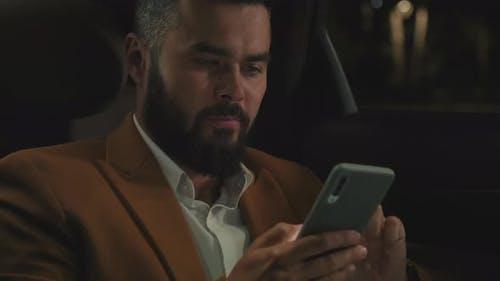 Man Using Smartphone In Car Backseat
