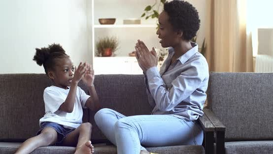 Thumbnail for Mom and Daughter of African Ethnicity Clap Their Hands Sitting on Sofa at Home in Living Room