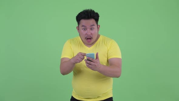Thumbnail for Happy Young Overweight Asian Man Using Phone and Getting Good News