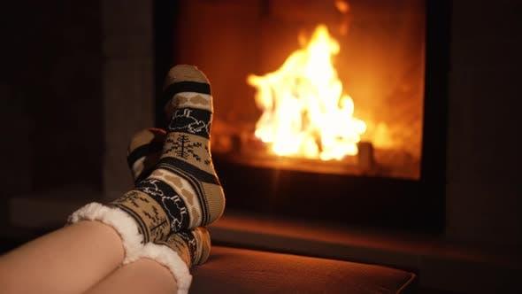 Pieds d'une femme assise près de la cheminée