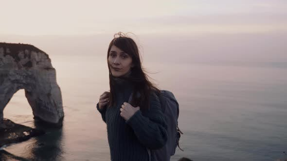Thumbnail for Beautiful Calm Tourist Woman Looking at Camera, Turning To Watch Gorgeous Sunset Over Etretat Cliffs