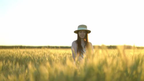 Woman Walking in a Field with Open Arms