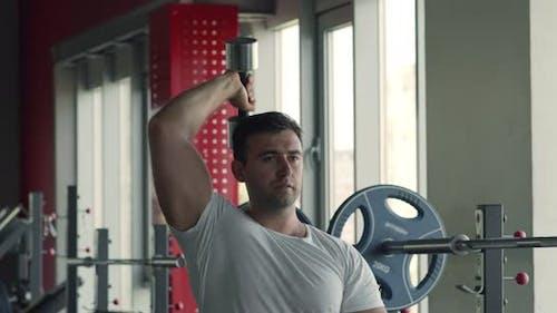 Muskulöser Mann mit Hantel im Fitnessstudio trainieren, Trizeps üben, Bizepsmuskeln Workout
