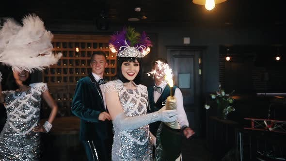 Retro Theme Party - Young People Having Fun and Dancing - A Woman Holding a Huge Bottle of Champagne