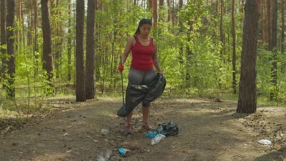 Thumbnail for Black Female Volunteer Picking Garbage in Woodland