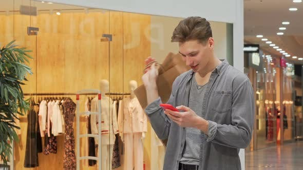 Thumbnail for Young Man Smiling Using Smart Phone While Shopping at the Mall