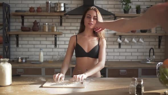 Thumbnail for Young Sexy Naked Girl Cooking in the Kitchen. Male Hands Remove the Flour Stain From the Female Lips