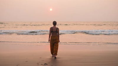 Woman Tourist Walking on the Beach Near the Ocean at the Sunset India Ocean