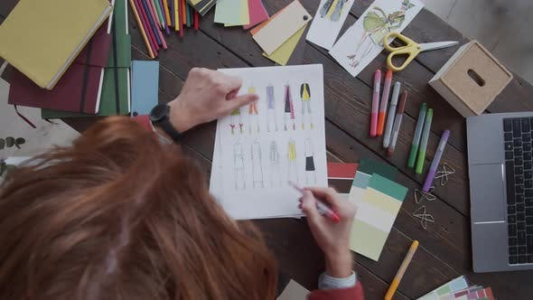 Thumbnail for Timelapse of Male Designer Coloring Fashion Sketches with Pencils